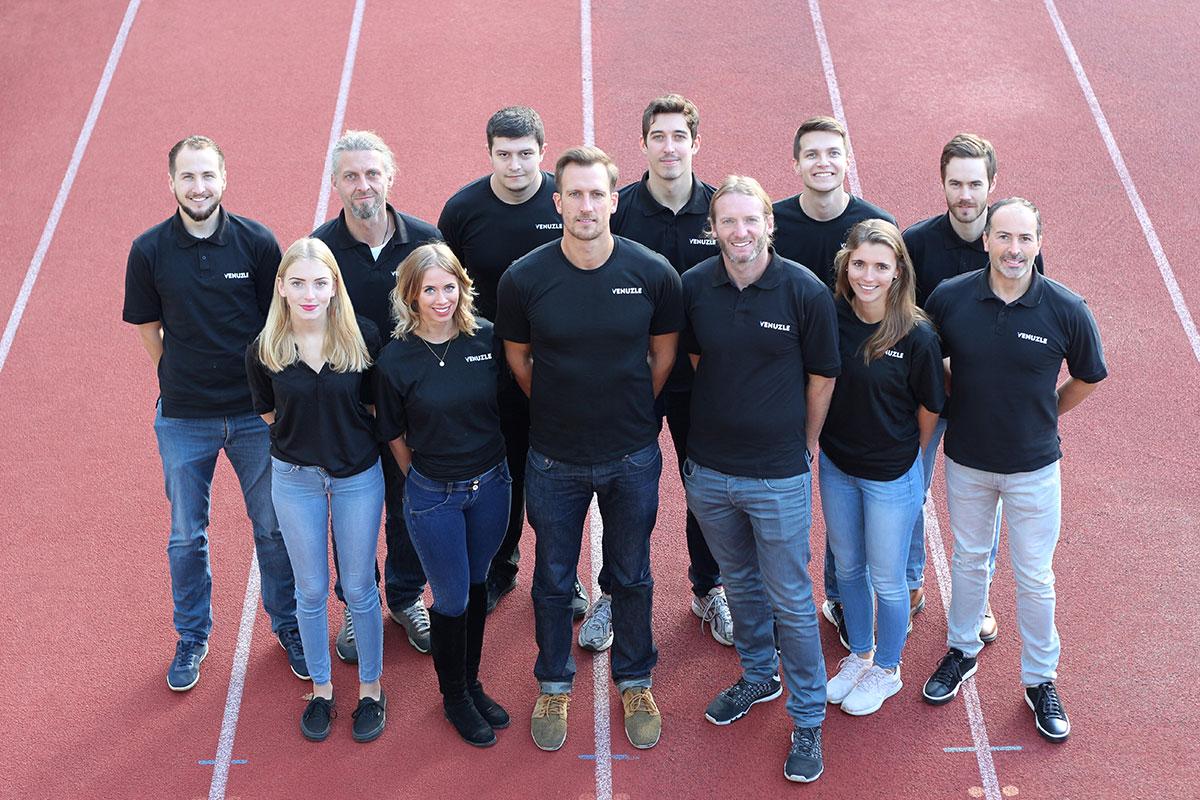 Venuzle Teamfoto mit 12 Personen mit schwarzem Venuzle Team Shirt, die auf einer roten Laufbahn in Graz stehen